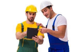 two plumbers looking at a clipboard